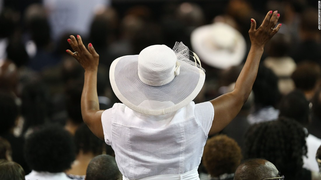 A mourner raises her hands in prayer.