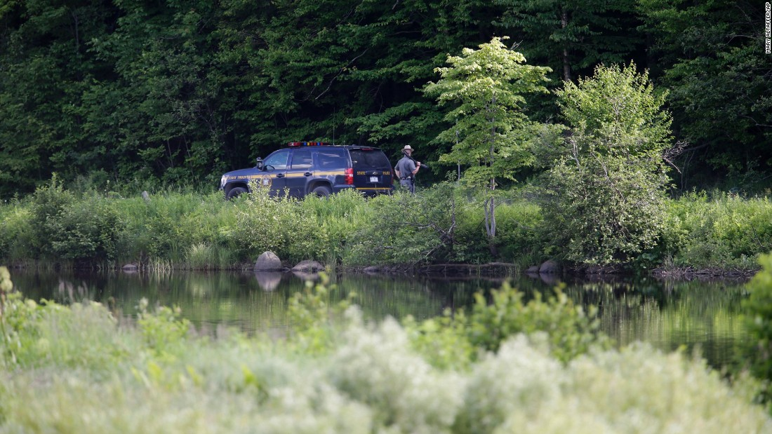 A New York State Police officer stands guard near the shooting scene in Malone on June 26.