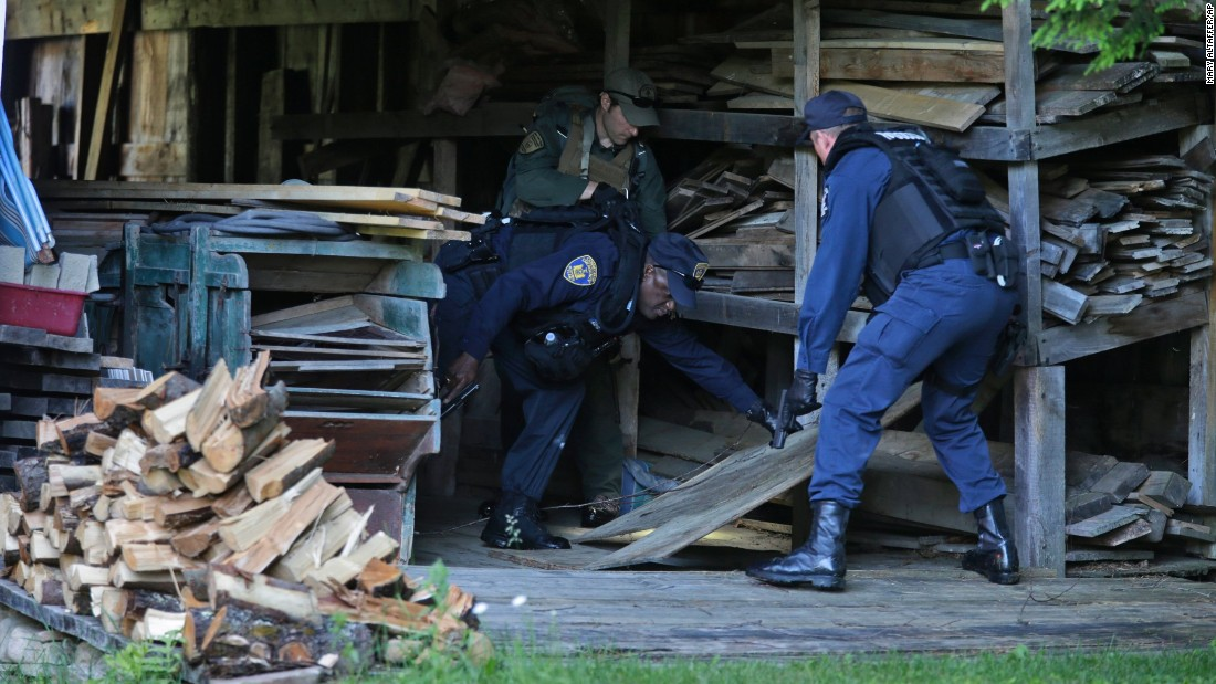 New York State Department of Corrections officers and a forest ranger, back, search a barn in Owls Head, New York, on June 26.