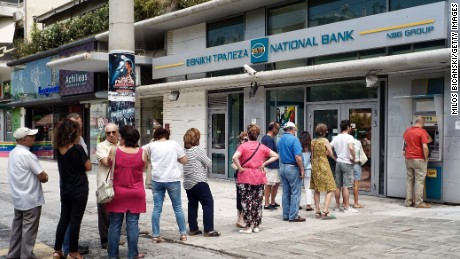 Greeks line up Sunday to withdraw cash at an ATM in Athens.