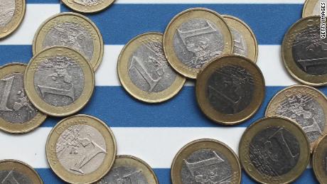 Euro coins over Greek flag