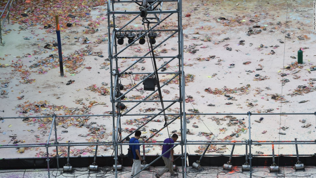 Two men walk at the explosion site of the water park in the Pali district, in New Taipei City, on June 28.