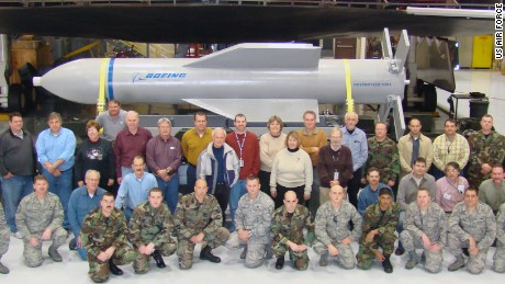 Weapon specialists gather in front of a mock up of the Massive Ordnance Penetrator and the B-2 weapons load trainer at Whitman Air Force Base, Missouri.