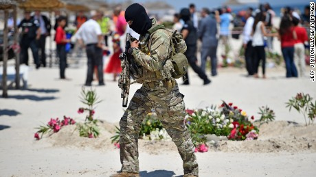 Armed guards patrol Marhaba beach during a visit by British Home Secretary Theresa May on June 29.