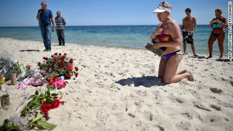 Holidaymakers react as people lay flowers on Marhaba beach, where 38 people were killed in a terrorist attack last Friday, on June 30, 2015 in Sousse, Tunisia.