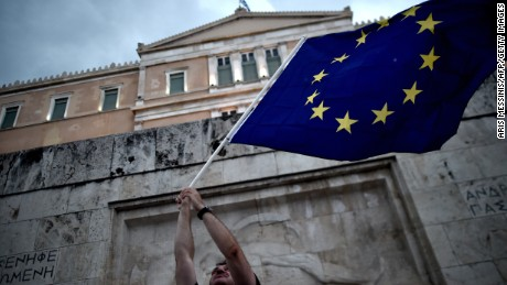 A pro-European Union protester waves an EU flag during a demonstration in front of the parliament in Athens on June 30, 2015. 2015.   Thousands of people rallied in Athens in support of a bailout deal with international creditors which has been rejected by Prime Minister Alexis Tsipras, leaving Greece on the brink of default.  AFP PHOTO / ARIS MESSINIS        (Photo credit should read ARIS MESSINIS/AFP/Getty Images)