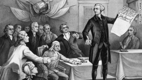 John Hancock, president of the Continental Congress is the first to put his signature to the Declaration of Independence, watched by fellow patriots Robert Morris, Samuel Adams, Benjamin Rush, Richard Henry Lee, Charles Carroll, John Witherspoon, John Adams and Edward Rutledge.
