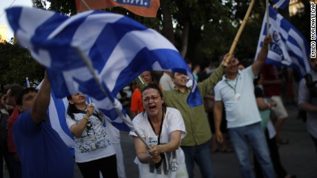 A supporter of the No vote waves a Greek flag after the referendum's exit polls at Syntagma square in Athens, Sunday, July 5.