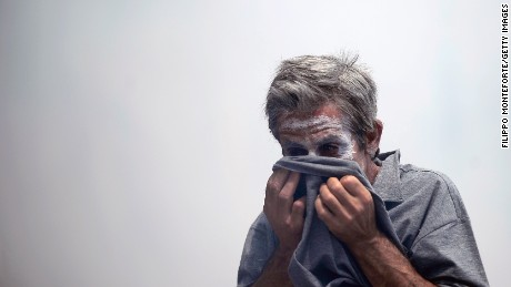 A demonstrator protects his face from teargas thrown by riot police in front of the Greek parliament on June 29, 2011 during a 48-hour general strike protest against the bankruptcy-threatened government which is desperately trying to push through sweeping austerity cuts. Amid angry street protests, MPs approved 28.4 billion euros ($40.7 billion) in spending cuts, unlocking a 12-billion-euro payout from the European Union and the International Monetary Fund.