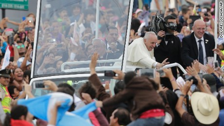The Pope greets supporters from aboard the Popemobile in downtown Quito on Sunday, July 5.
