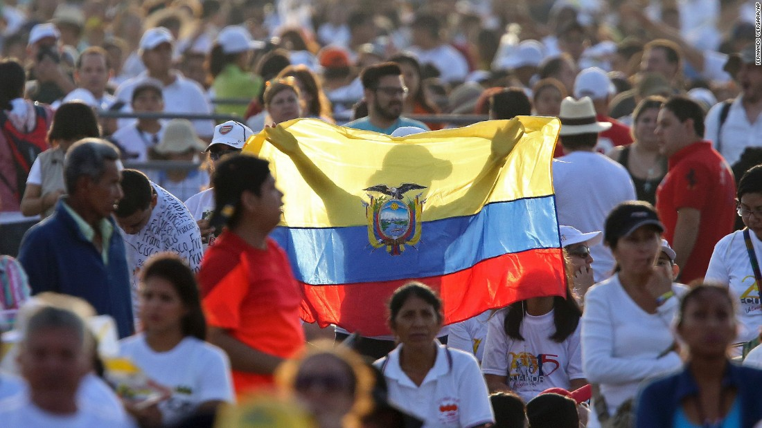 A woman holds up an Ecuadorian flag in a crowd of people waiting in Guayaquil on July 6. More than 1 million were expected to attend the Mass. Many camped out overnight.
