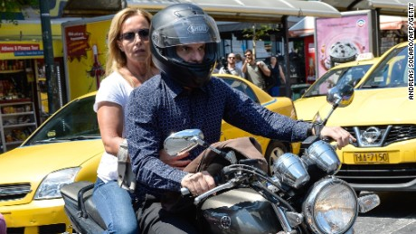 Caption:Greece's maverick finance minister Yanis Varoufakis, who announced his surprise resignation leaves the Ministry of Finance with his wife Danai on the back of a motorbike downtown Athens, on July 6 2015. Germany dismissed Greece's bid to clinch a quick new debt deal after the country delivered a resounding 'No' to more austerity, appearing little moved by the surprise resignation of the Greek finance minister. AFP PHOTO / ANDREAS SOLARO (Photo credit should read ANDREAS SOLARO/AFP/Getty Images)