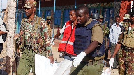 Kenya Police officers carry a body in Mandera, Kenya, Tuesday, July 7, 2015.