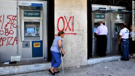 A woman passes an ATM machine as people queue to withdraw money in Thessaloniki, Greece on July 6, 2015.