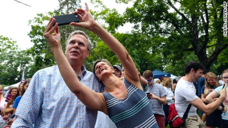 Republican presidential candidate former Florida Gov. Jeb Bush, left, has a selfie taken with a supporter while participating in the Fourth of July Parade festivities in Amherst, N.H.,,Saturday, July 4.
