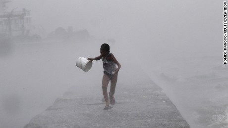 A boy runs as heavy rains and high waves brought by typhoon Linfa, locally named Egay, crash along a breakwater along Manila Bay at a slum area in Baseco, Tondo in Manila July 6.