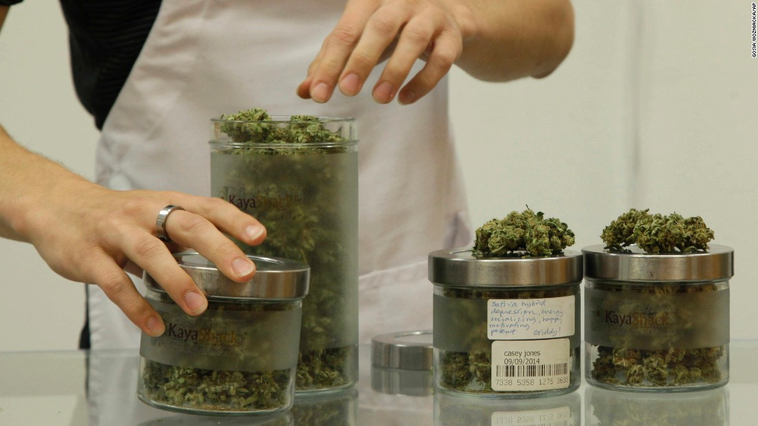 An employee at Kaya Shack, a Portland, Oregon, medical marijuana dispensary, showcases three types of marijuana sold at the shop on June 26, 2015. Oregon legalized recreational marijuana use on July 1, 2015.
