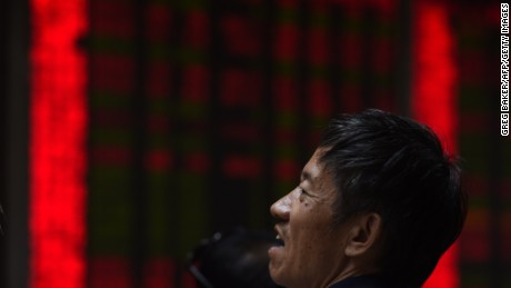 A man sits in front of screens showing stock market movements at a securities company in Beijing on July 9, 2015. China's market regulator has barred major shareholders and executives of listed companies from selling their shares for the next six months, it said in a statement, the latest government action to stem a slide in the markets. AFP PHOTO / GREG BAKER (Photo credit should read GREG BAKER/AFP/Getty Images)