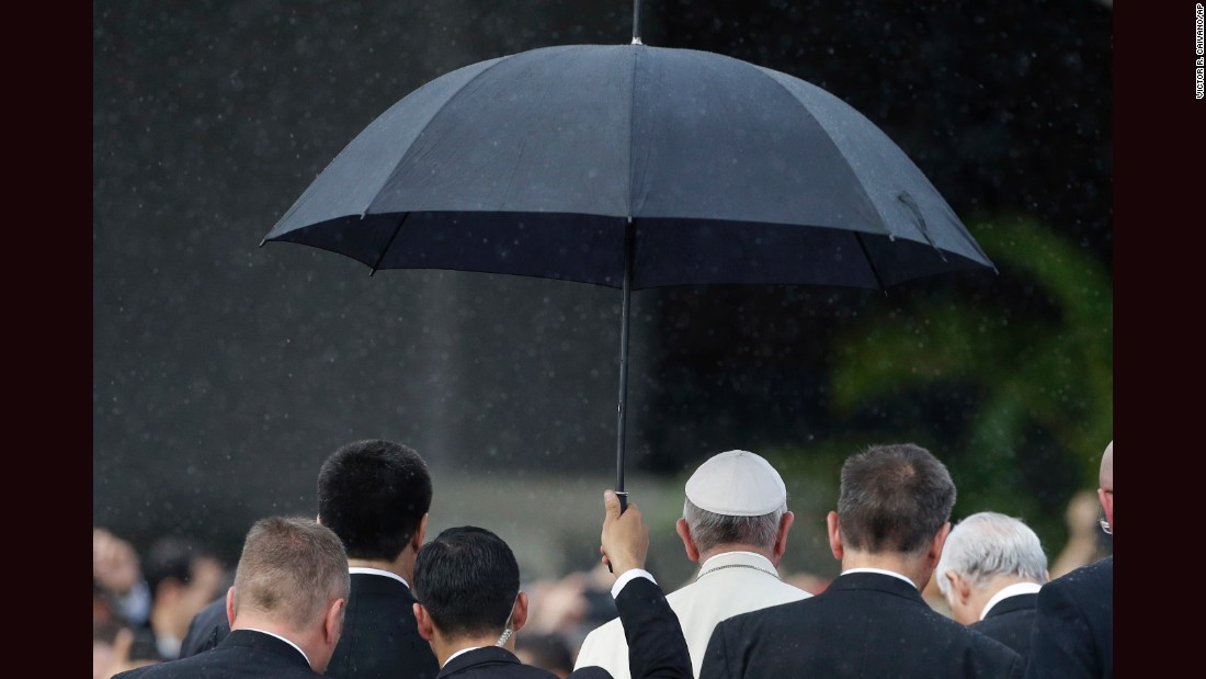 A member of the security detail holds an umbrella over Pope Francis upon his arrival in Asuncion, Paraguay, Friday, July 10.