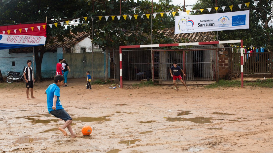 Children play soccer on the grounds where Pope Francis will speak.