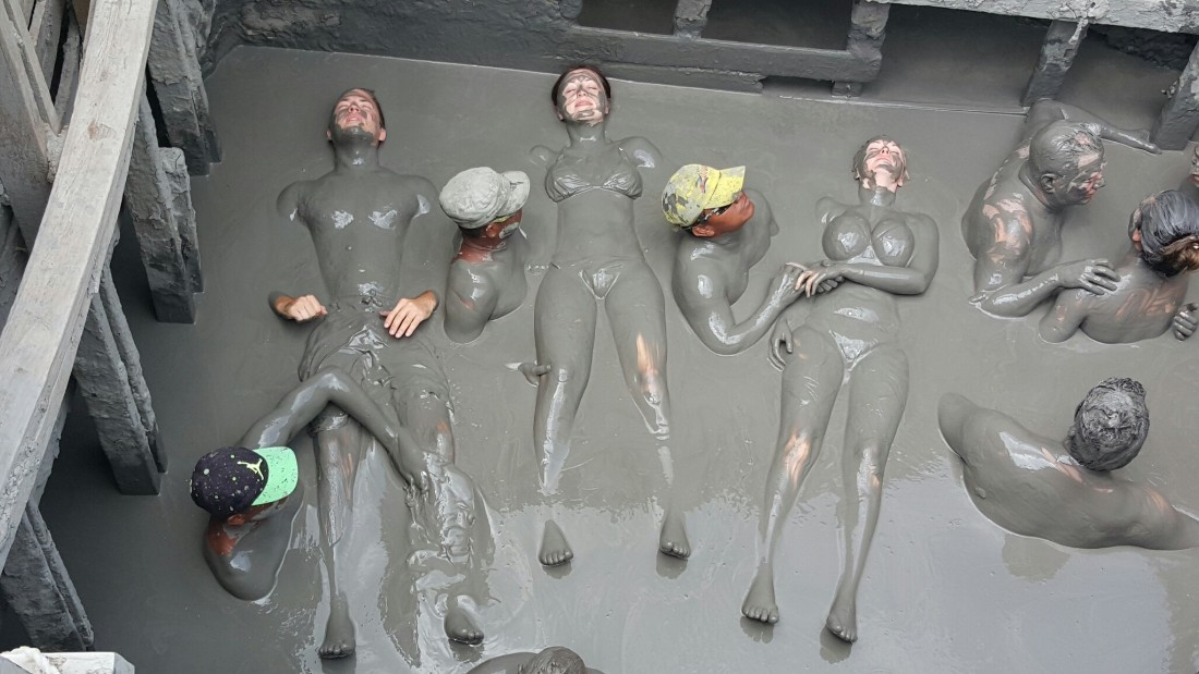 Once inside the volcano, attendants slather bathers in mud.