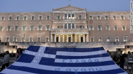 Demonstrators display the Greek flag in front of parliament on July 15, 2015 in Athens, Greece. Anti-austerity protesters hurled petrol bombs at police in front of Greece's parliament as lawmakers began debating deeply unpopular reforms needed to unlock a new eurozone bailout. Riot police responded with tear gas against dozens of hooded protesters who set ablaze parts of Syntagma square in central Athens