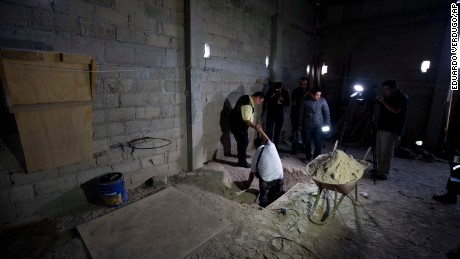 """Journalists exit the tunnel where according to authorities drug lord Joaquin """"El Chapo"""" Guzman made his escape from the Altiplano maximum security prison in Almoloya, west of Mexico City, July 14."""
