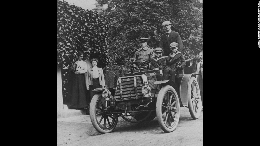 Ford's 1903 Model A, with a base price of $750, was enough of a success to allow the company to grow. Here, a family proudly sits in one while women look on from the side of the road.