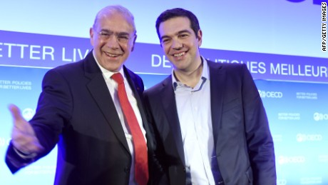 """OECD Secretary General Angel Gurria (L) and Greek Prime Minister Alexis Tsipras pose during Tsipras' visit to the OECD headquarters in Paris, on March 12, 2015. Greece announced on March 12 that it has officially launched a partnership deal with the OECD to draw up economic reforms, which Prime Minister Alexis Tsipras said would help rebuild trust with international creditors. The slogan behind reads """"Better politics for better lives"""". AFP PHOTO / ERIC FEFERBERGERIC FEFERBERG/AFP/Getty Images"""