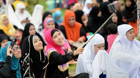 "Young Muslim devotees take a ""selfie"" prior to Friday prayers to mark the end of the holy month of Ramadan and the start of Eid al-Fitr at a park in Manila on July 17, 2015. Muslims around the world have begun to celebrate Eid al-Fitr, the first day of Shawwal according to Islamic calendar, marking the end of fasting month of Ramadan.      AFP PHOTO / TED ALJIBE        (Photo credit should read TED ALJIBE/AFP/Getty Images)"