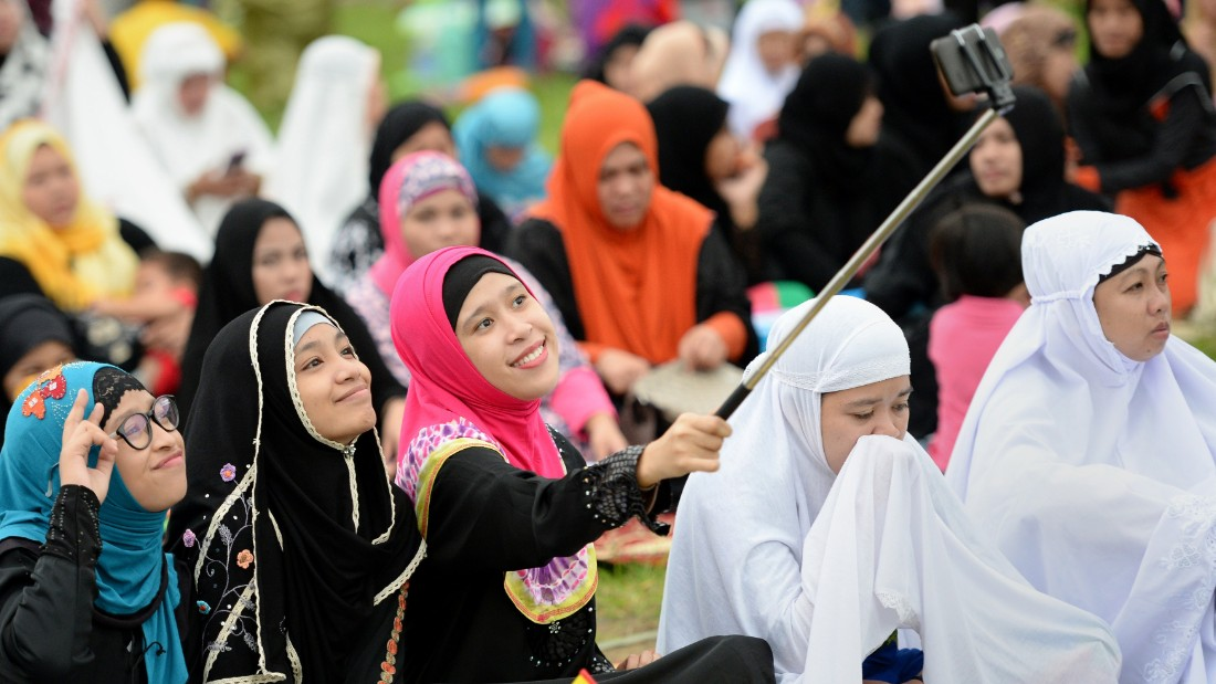 """Young Muslim devotees take a """"selfie"""" prior to Friday prayers to mark the end of the holy month of Ramadan and the start of Eid al-Fitr at a park in Manila on July 17, 2015. Muslims around the world have begun to celebrate Eid al-Fitr, the first day of Shawwal according to Islamic calendar, marking the end of fasting month of Ramadan.      AFP PHOTO / TED ALJIBE        (Photo credit should read TED ALJIBE/AFP/Getty Images)"""