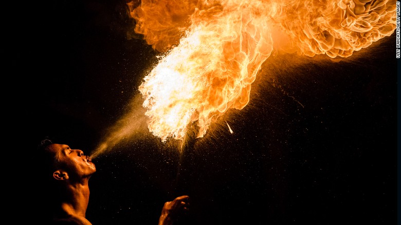 A Muslim man breathes fire during a game of fire football, known as 'bola api'