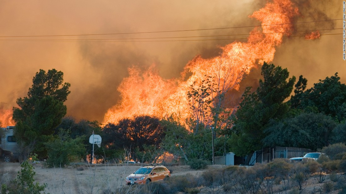 Flames rise over a cluster of homes in Oak Hills on July 17.