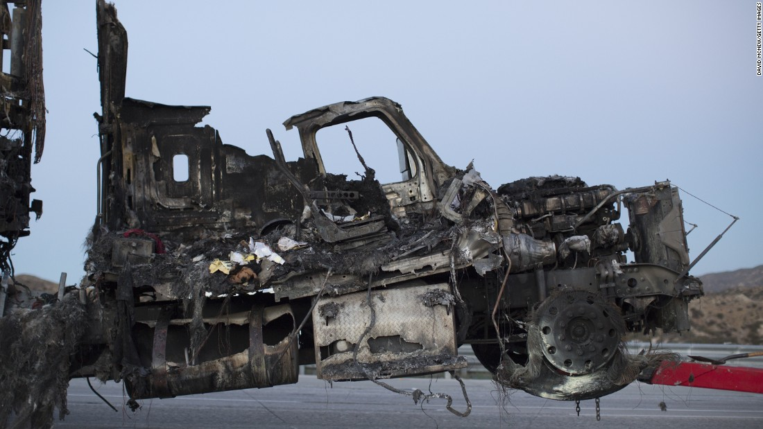 The scorched remains of a truck destroyed by the North Fire are towed away near Victorville on July 17.