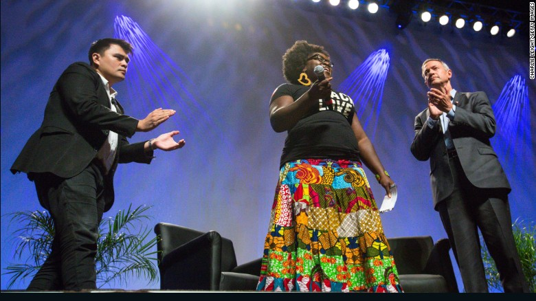Former Maryland Gov. Martin O'Malley, right, and moderator Jose Antonio Vargas, left, listen to Tia Oso, the National Coordinator for the Black Immigration Network, during an interruption to O'Malley's speech at the Netroots Nation 2015 Presidential Town Hall with at the Phoenix Convention Center July 18, 2015 in Phoenix, Arizona.