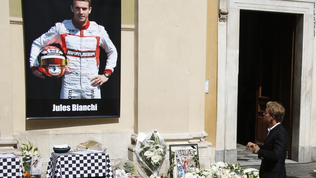 Mercedes driver Nico Rosberg pauses at the main entrance to the cathedral where tributes had been lain below a portrait of Jules Bianchi in his Marussia racing suit.