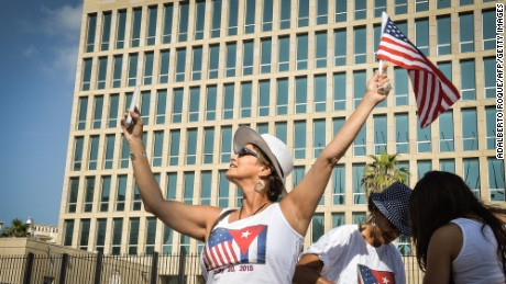 A tourist makes a selfie holding a US Flag in front of the US Embassy in Havana, on July 20, 2015.