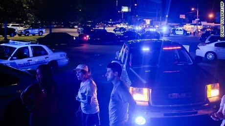 Bystanders look on as emergency personnel respond.