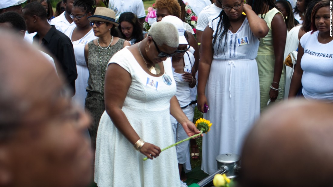 Shavon Bland, the sister of Sandra Bland, holds a flower over her gravesite on July 25.