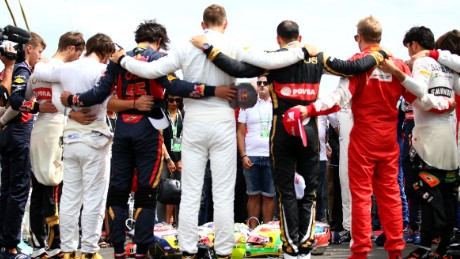 F1 drivers linked arms with members of Jules Bianchi's family to hold a minute's silence for the French driver.
