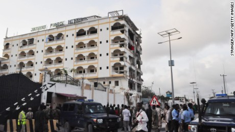 People stand in front of the damaged Jazeera Palace hotel following a suicide attack in Mogadishu on July 26, 2015. Somalia's Shebab insurgents killed at least six people today when they detonated a huge car bomb at a heavily guarded hotel in the capital Mogadishu housing diplomatic missions, officials and witnesses said. AFP PHOTO / STRINGER (Photo credit should read -/AFP/Getty Images)