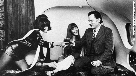 American magazine publisher Hugh Hefner and his companion, American model and actor Barbi Benton, relax on a bed while a stewardess attends to them in the private quarters of Hefner's DC-9 jetliner, 'The Big Bunny' en route to Heathrow.