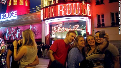 """Tourists take a """"selfie"""" in front of the Moulin Rouge cabaret in Paris, France, July 24, 2015."""