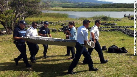 Police carry a piece of debris from an unidentified aircraft found off the coast of Reunion island.