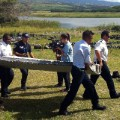 Police carry a piece of debris from an unidentified aircraft found in the coastal area in the east of the French Indian Ocean island of Reunion.