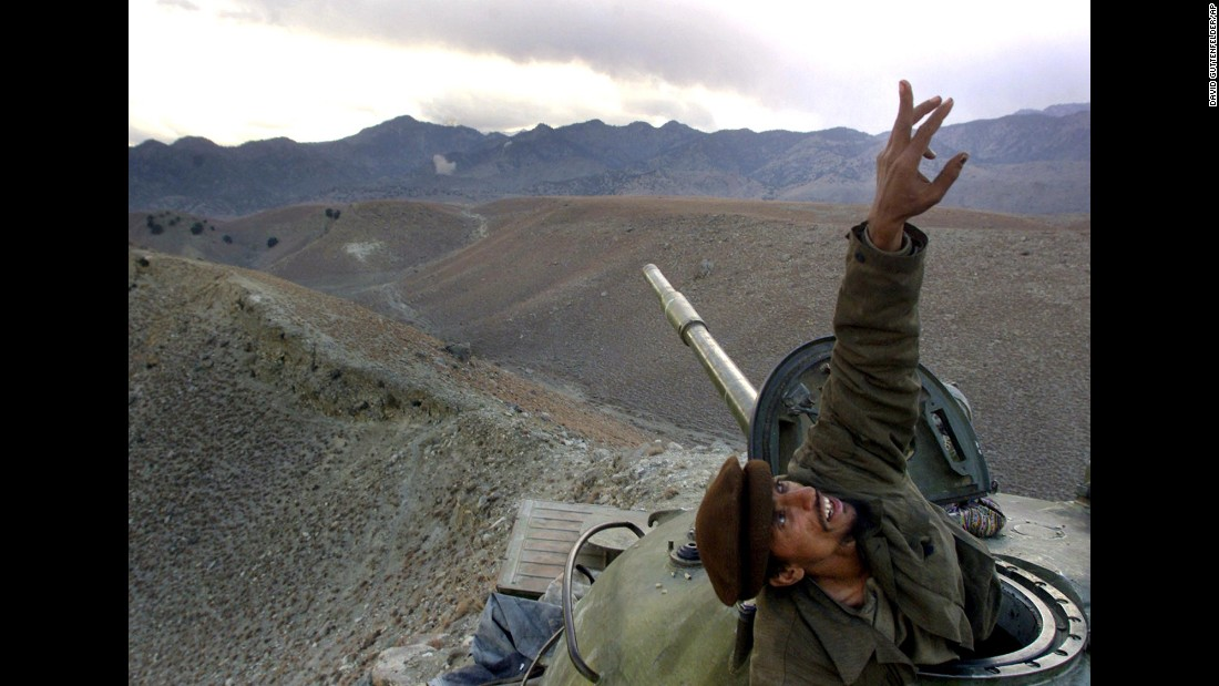 An Afghan anti-Taliban fighter pops up from his tank to spot a U.S. warplane bombing al Qaeda fighters in the Tora Bora region of Afghanistan on December 10, 2001. After massive U.S. bombardment as a part of Operation Enduring Freedom, the Taliban lost Afghanistan to U.S. and Northern Alliance forces.