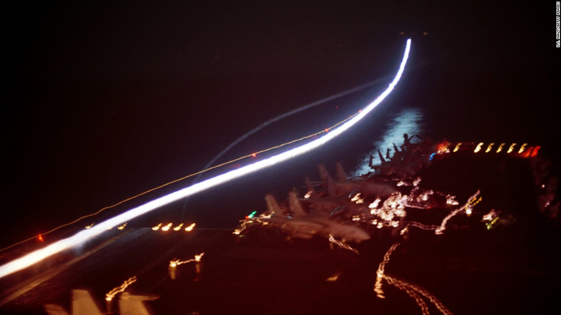 After the 9/11 attacks, the United States conducted military strikes against al Qaeda training camps and military installations of the Taliban regime. In this long-exposure photo, a U.S. Navy fighter jet takes off from the deck of the USS Enterprise on October 7, 2001.
