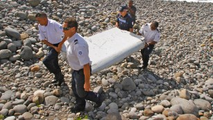Police carry a piece of debris on Reunion Island, a French territory in the Indian Ocean, on Wednesday, July 29. A week later, authorities confirmed that the debris was from Malaysia Airlines Flight 370, which disappeared on March 8, 2014.