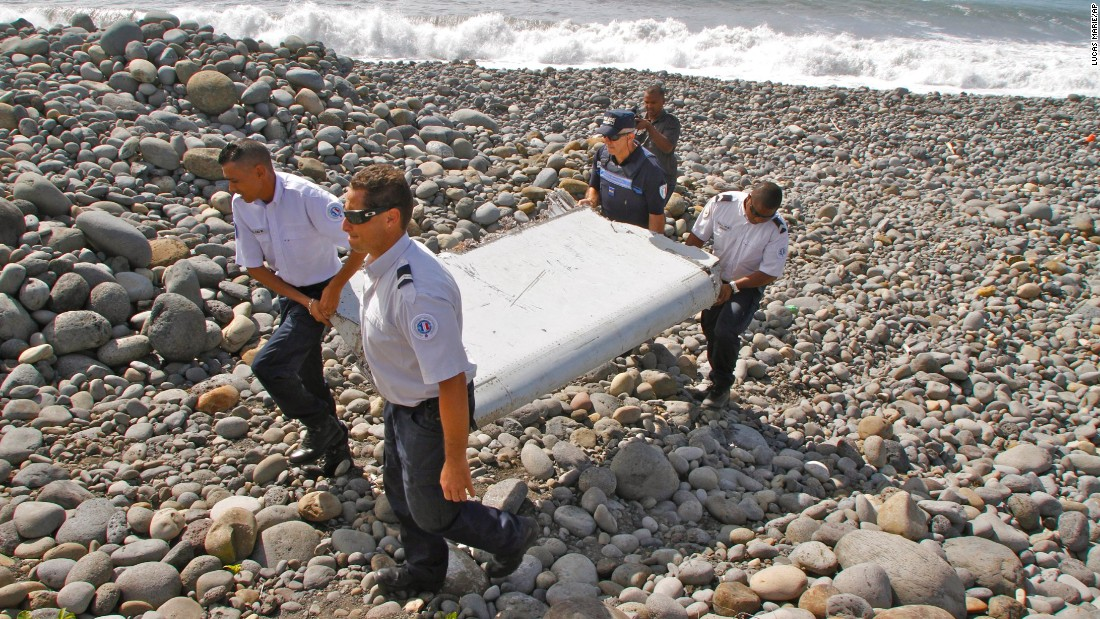 "On July 29, police carry a piece of <a href=""http://www.cnn.com/2015/07/30/world/gallery/debris-found-reunion-island/index.html"" target=""_blank"">debris on Reunion Island,</a> a French territory in the Indian Ocean. A week later, authorities confirmed that the debris was from the missing flight."