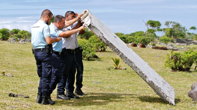 "In this photo dated Wednesday, July 29, 2015, French police officers inspect a piece of debris from a plane in Saint-Andre, Reunion Island. Air safety investigators, one of them a Boeing investigator, have identified the component as a ""flaperon"" from the trailing edge of a Boeing 777 wing, a U.S. official said. Flight 370, which disappeared March 8, 2014, with 239 people on board, is the only 777 known to be missing. (AP Photo/Lucas Marie)"